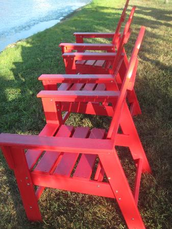 Santa's Lakeside Cottages: Red chairs by the lake