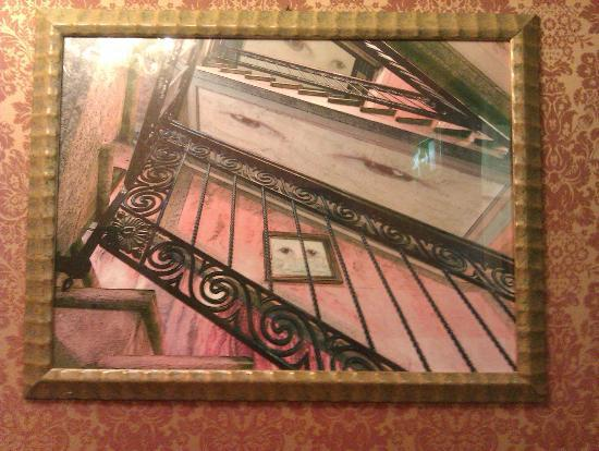 Hotel La Fenice Et Des Artistes: One of the more surreal paintings hanging on the staircase of the staircase