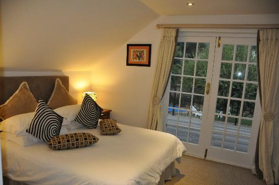 The Coach House: Part of our bedroom with view to the terrace and pool/garden