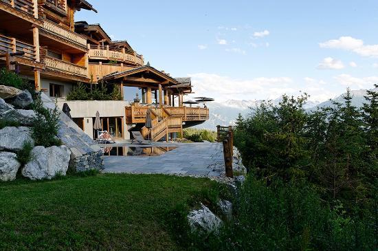 LeCrans Hotel & Spa : Une partie de l'hôtel depuis l'angle droit avec piscine extérieure du SPA
