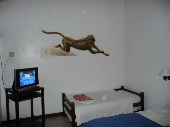 Pousada Blue Marlin: Hotel room w/cot, (queen size bed not shown). Wall mural is a handpainted pic of an onça (cheet