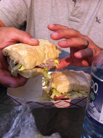 Grateful Deli: subs come cut in half and wrapped in a to go container.