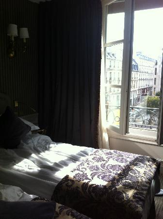La Maison Favart: Bed and street view of Paris from the room