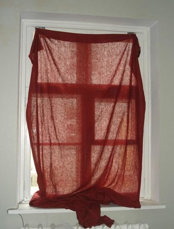 Knight House: cortinas atadas con grapas o cuerdas a la ventana