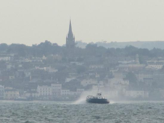 Ryde Harbour: A hovercraft heading to the mainland with Ryde in the background