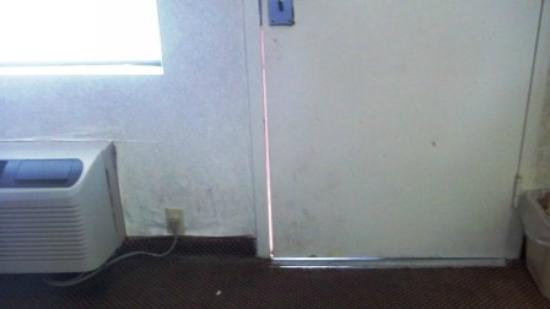 Super 8 Fredericksburg: Door closed tightly, didn't seal. Can see more falling wallpaper in room.