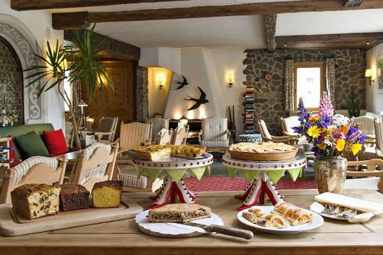 Hotel Chesa Randolina: Kaminhalle mit Kuchenbuffet