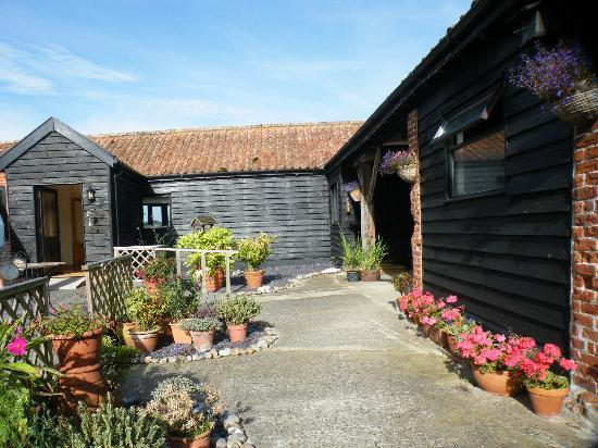 Cowshed Holidays: Courtyard at Walnut Tree Farm. Rooms and terraced area are on the left.