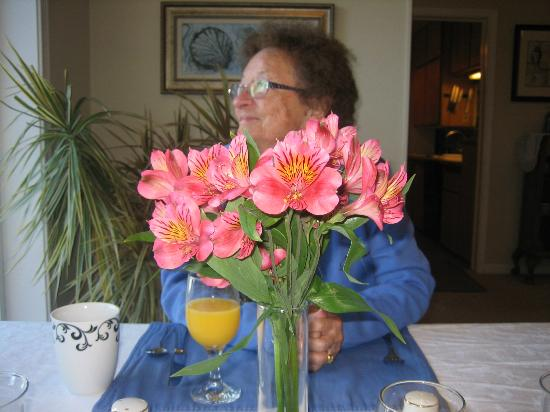 Ocean House Bed and Breakfast: My mom taking in the view and fresh flowers on the table before being served breakfast!