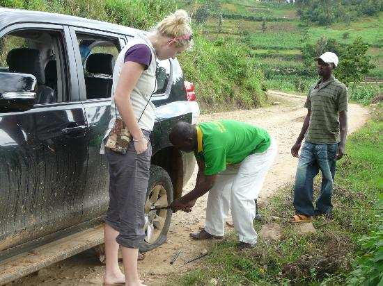 Le Bambou Gorilla Lodge: Oups! A flat tire! Emmanuel does not want to get dirty!