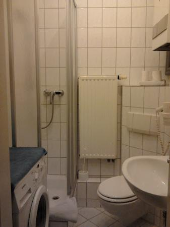 A bed Privatzimmer Dresden: Shared bathroom with washing machine
