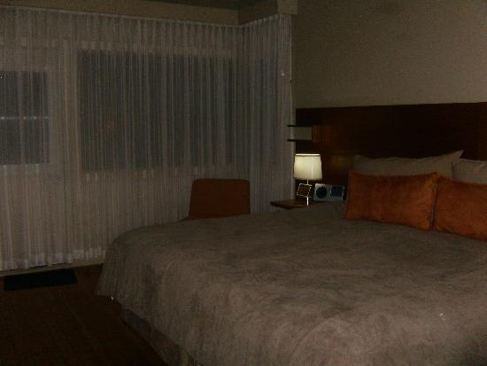 The Juniper Hotel: king sized bed, lamps, bedside table and occasional chair