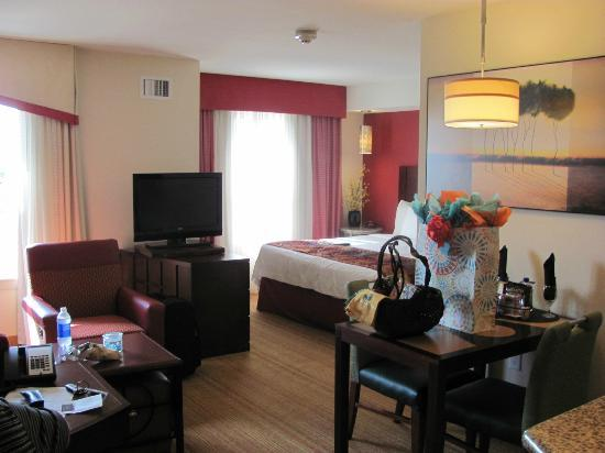 Residence Inn Dallas Plano/The Colony: TV swivels from living space to bedroom - Presents and basket not included on table in kitchen a