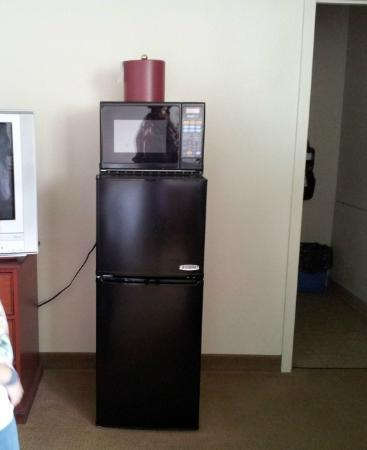 Pacific Beach Resort & Conference Center: fridge with freezer, basic tv set, and bathroom to the right