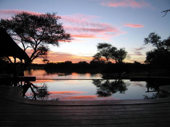 Okonjima Game Reserve : Grand African Villa, sunset overlooking the waterhole, Okonjima, Namibia