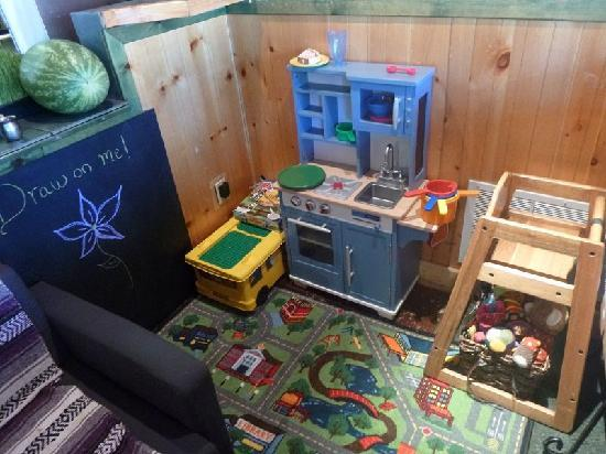 Simple Bliss Vegan Cafe: kiddo area with chalkboard, legos, kitchen and stuffed animals. The kitchen doubles as our emplo