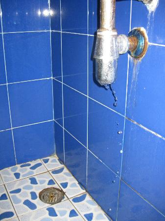 Scandinavian Residence: Leaking rusted sink and the filthy shower drain