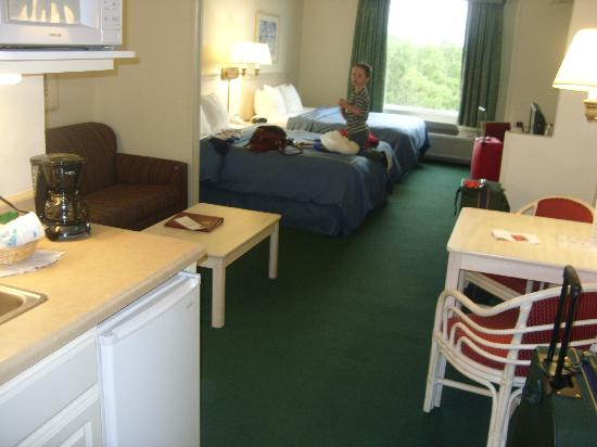 Comfort Suites Maingate East: Room showing beds, seating area and a corner of the fridge