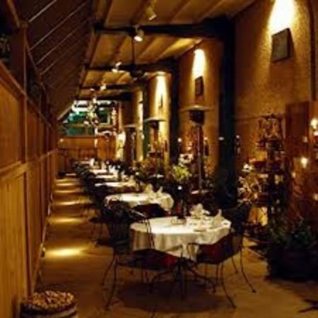 Warehouse Bistro: The Patio Which is Adorned With Foliage and Wine Bottle Art.