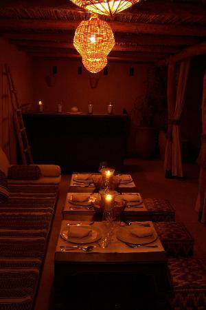 Riad Snan13 : A view of the terrace dining area at night.