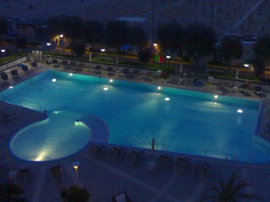 Miramare Hotel & Spa: Vista sul giardino interno con piscina fronte mare, illuminazione notturna di alto effetto.