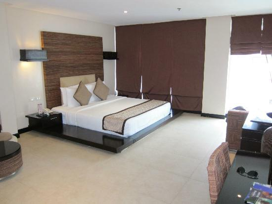 Two Seasons Boracay Resort: low queen-sized bed...drapes covering wall to ceiling glass windows
