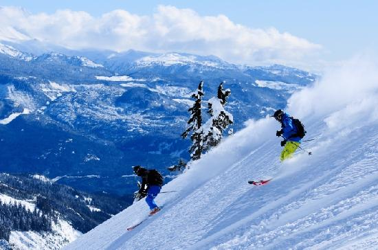 Whistler, Canada: A couple enjoys a picture-perfect day while skiing on fresh snow. Photo credit: Mike Crane