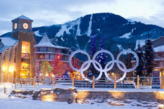 The Olympic Rings glow on a snowy winter evening in Whistler Village with moutnain views in the
