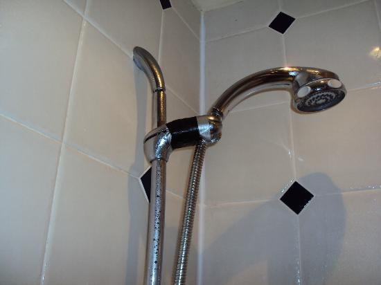 The Old Vicarage: Duck tape holding up shower head.