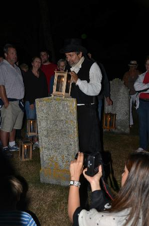 Annapolis Royal Candlelight Graveyard Tour: Alan Melanson with lantern on a gravestone.