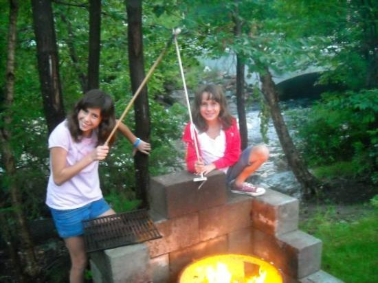 "Country Bumpkins Campground and Cabins: View from our cabin and kids enjoying toating marshmallows with their ""Moosemallow sticks."""