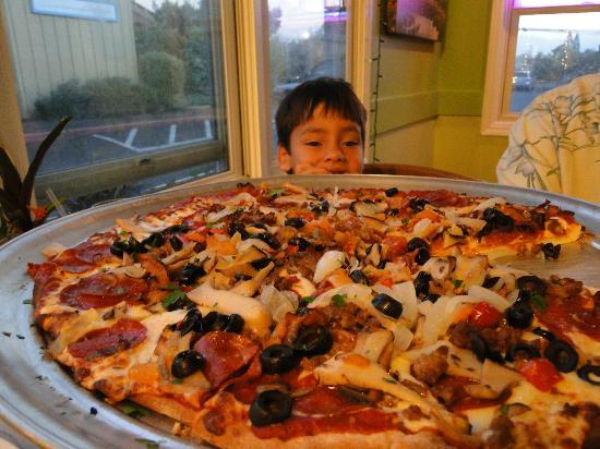 My kid sizing up my husband's pizza at Pau
