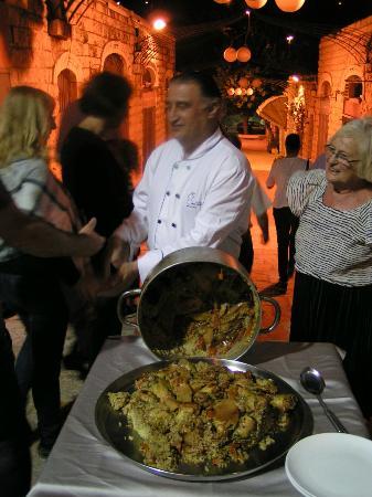 The Eucalyptus : Le chef du restaurant servant une paella lors d'un repas familial