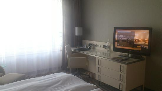 Pullman Berlin Schweizerhof: Desk and flat-screen tv