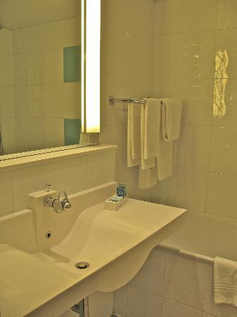 Novotel Bayeux : Small bathroom with tub shower and old fashioned hairdryer