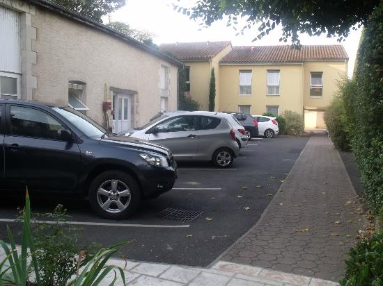 Hotel le Lion d'Or: small hotel car park with annex in the background