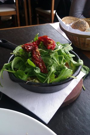 Minga: Provoleta tipo mediterránea con aceitunas negras, rúcula y tomates secos