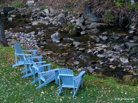 Grist Mill House : There are 4 Muskoka chairs set out by the stream.