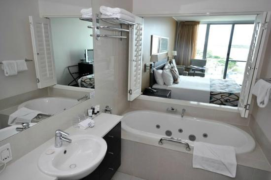 Ramada Hotel & Suites Ballina Byron: The bathroom, with shutters open, looking across the room and out to the view.