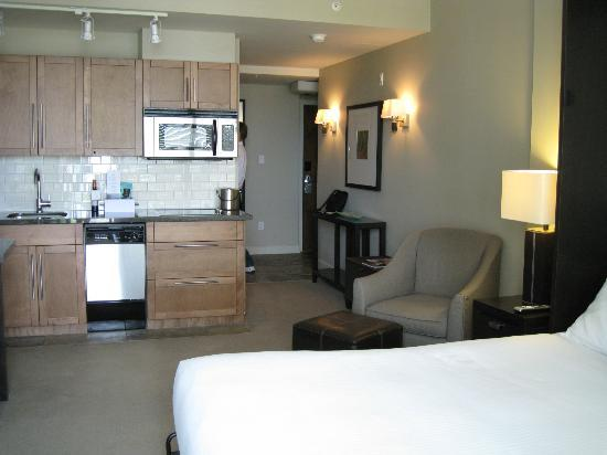 The Oswego Hotel: studio suite bed, chair, kitchen, entry hall