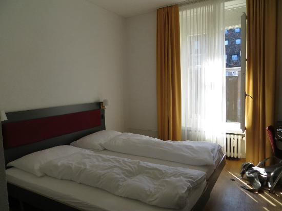 Hotel Kreuz Bern: View from door towards window - there is a tiny night stand next to bed.