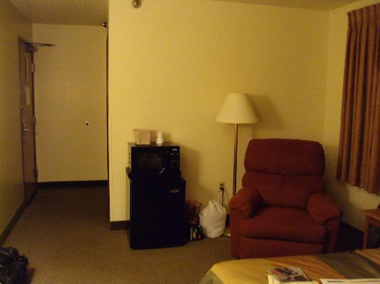 Super 8 Bloomington/Airport : Room with chair, microwave and fridge