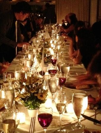 Long dramatic tables for the wedding dinner lit with hundreds of ...
