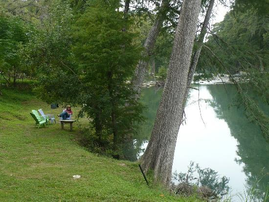 Gruene River Inn: The hotel lawn by the river. Notice the chairs with my wife sitting.