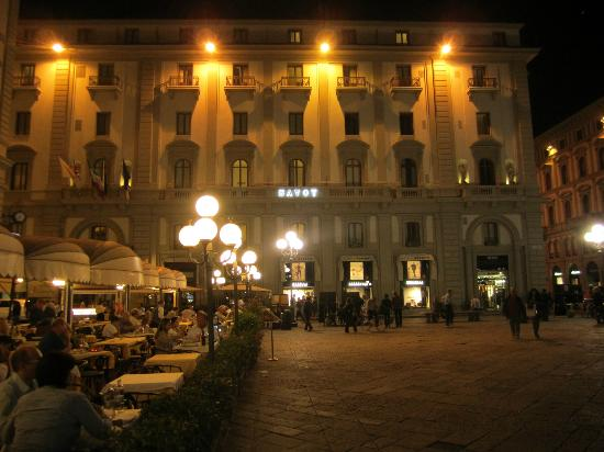 Hotel Savoy: The hotel at night. One of the several bars in the square can be seen on the left.