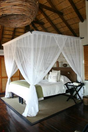 Impodimo Game Lodge: Bedroom in thatched cottage