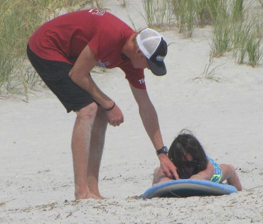 WB Surf Camp: He showed her how to lie on the board before they went down to the water.