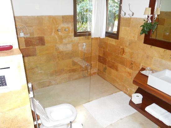Pousada Terra dos Goitis: Bathroom with stone wall and view to garden