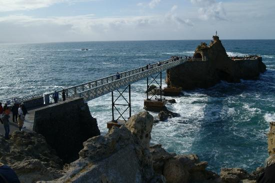 Rocher de la Vierge : a un lado, vista de la pasarela y la Virgen de la Roca, al fondo