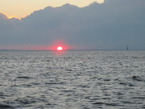 Blue Crab Chesapeake Charters : Sunset cruise of the Chesapeake with a firey red sun, about to disappear on the horizon.